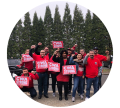 """A group of workers in front of a background of pine trees. They're wearing red shirts and holding signs that read """"CWA strong,"""" while some hold upraised fists."""